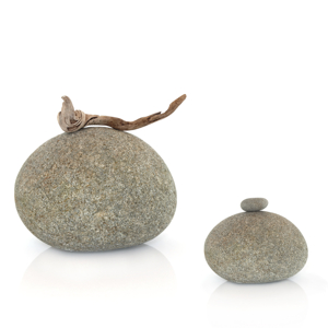 Zen abstract of two stones one with a piece of driftwood the other with a small stone balanced on the top, over white background.
